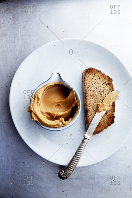 A plate with a slice of toast and peanut butter and a spreading knife shot from above,