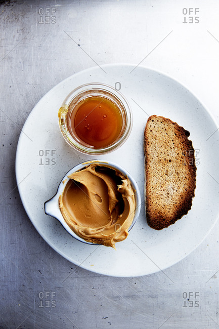 Plate with toast and peanut butter and honey on a kitchen counter,