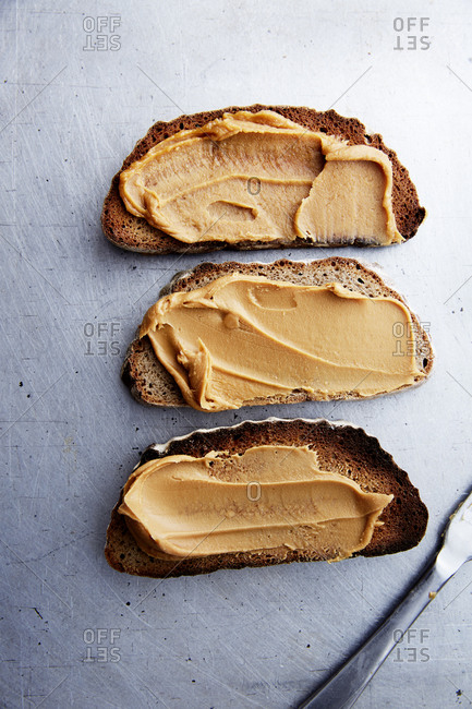 Three slices of toast with peanut butter on a kitchen counter,