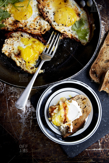 Fried eggs in a pan with fresh coriander and sourdough toast on a rustic background,