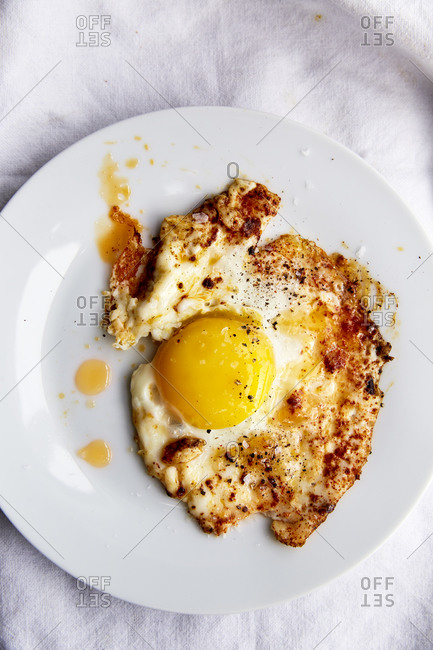 Fried egg in paprika chilli oil in a white plate on a white linen cloth,