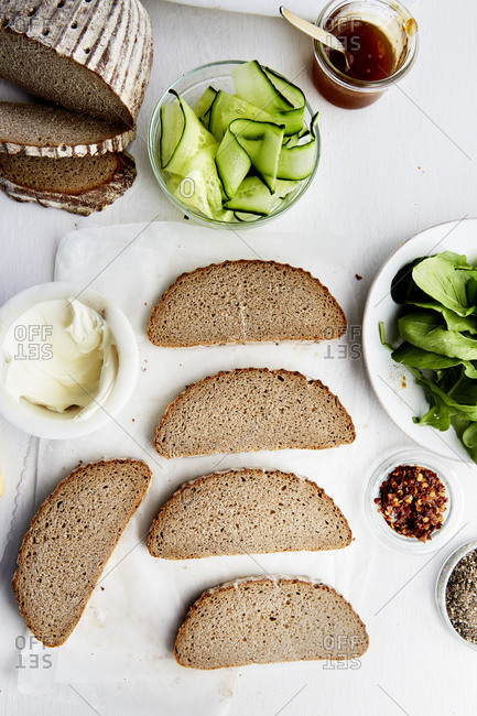 Sliced rye bread with various toppings, cucumber, cream cheese and chilli flakes on the side,