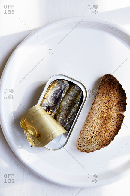 Open tin of sardines on a white plate,