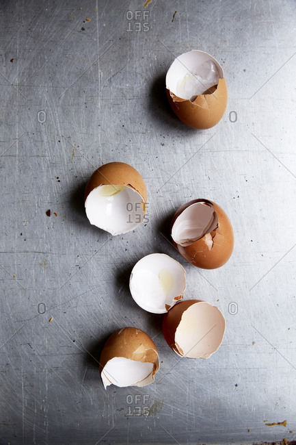 Empty egg shells on a stainless steel kitchen countertop,
