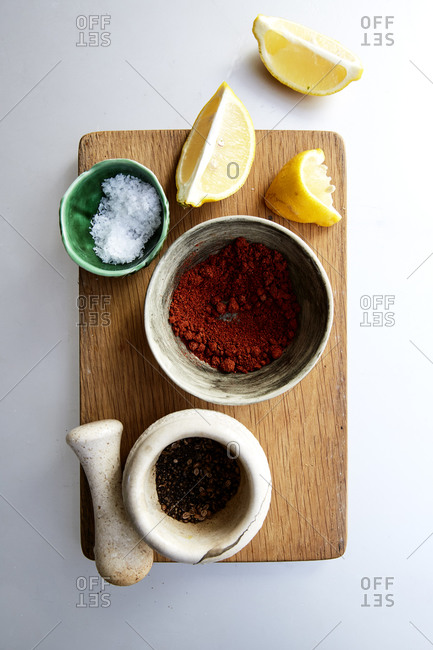 Spices and lemon wedges on a chopping board,