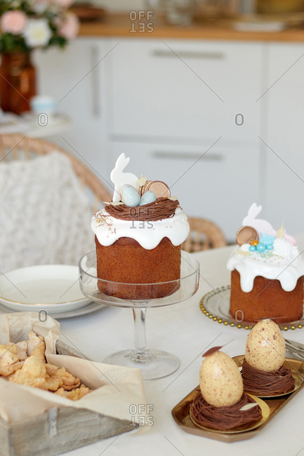 dessert sweets for chocolate eggs, Easter cake with rabbit, crunchy cookies angel wings