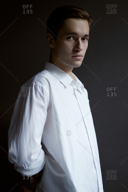 portrait of a young guy a man in a white shirt daylight