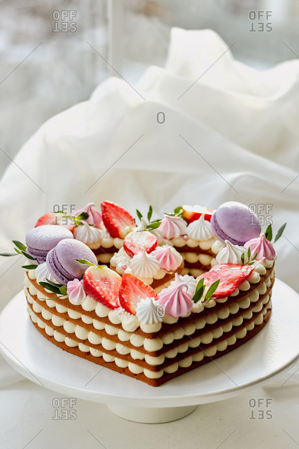 birthday tiramisu cake in the form of a heart with a cap of strawberries, macaroon, meringue