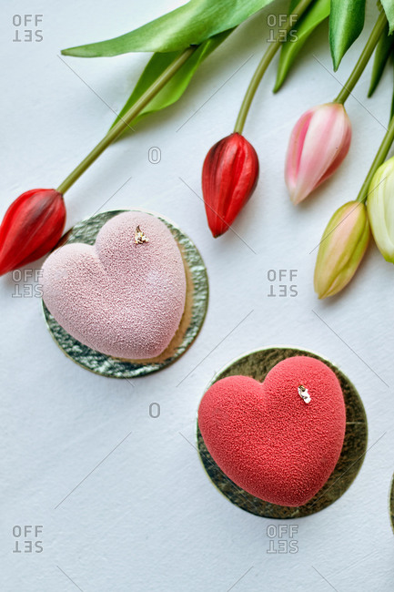 women's day Valentine mousse cake in the form of a heart with a matte surface and tulips