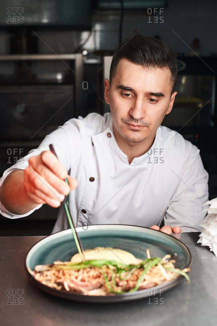 cook in a white jacket prepares food in chef kitchen of the hotel restaurant