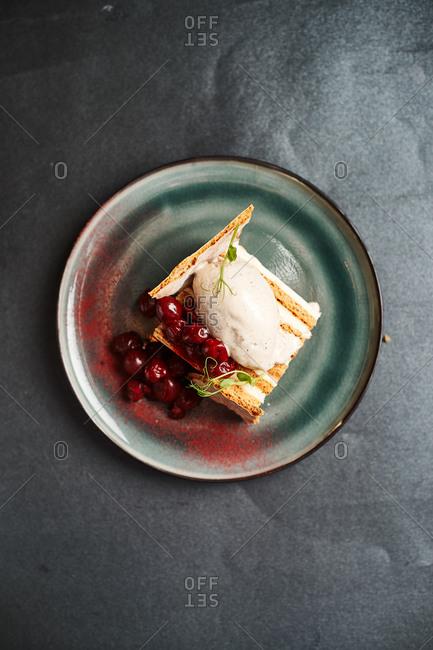 sweet cake made of sour cream, honey, cherries, ice cream on a dark background