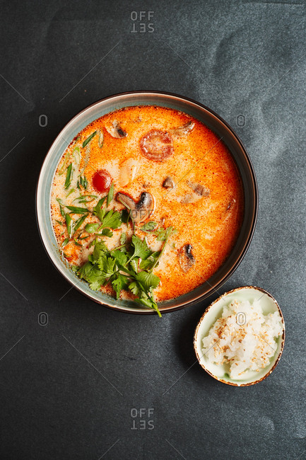 Asian Tom Yam soup with coriander, mushrooms, shrimp and a Cup of rice