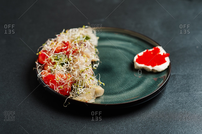 lunch smoked white fish salad with tomatoes, cucumber, red caviar, mayonnaise