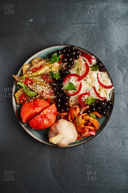 pickles for lunch on a plate cucumbers, cabbage, tomatoes, peppers, berries, garlic, mushrooms and sesame