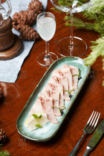 dinner vodka and white fish carpaccio with lemon on a ceramic plate