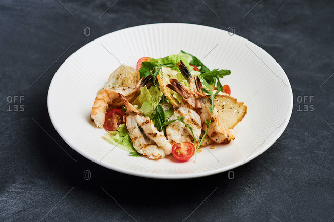 lunch Caesar salad with king prawns, tomatoes, croutons, crackers, greens, rucola, Parmesan