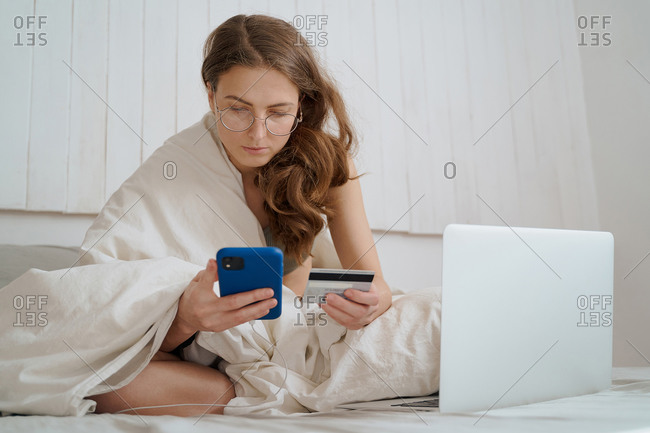 woman using smartphone and credit card to buy clothes online, laptop on bed
