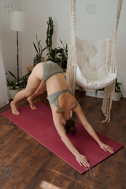 woman does yoga asana exercises and stretches at home using an app on her smartphone, laptop, athletic body