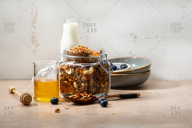 Homemade granola in a jar and a bottle of milk, breakfast