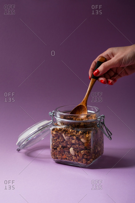 Scooping homemade granola from a jar