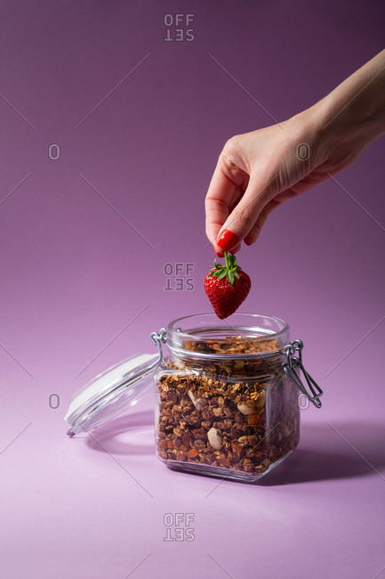 Hand holding fresh strawberry over jar of granola