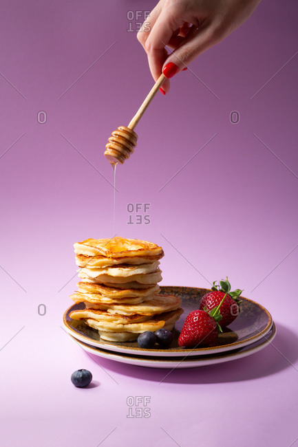 Pancake stack and hand with wooden stick pouring honey