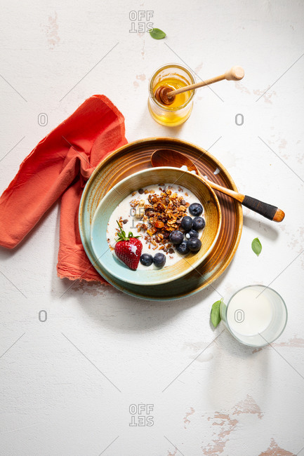 Overhead view of bowl with breakfast cereal with berries and milk