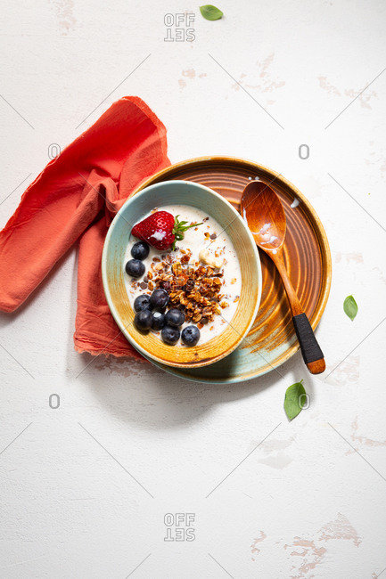 Overhead view of bowl with breakfast cereal with berries and milk on light table