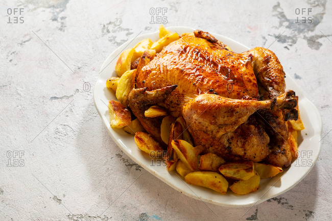 Close up of chicken with potatoes on plate on light surface