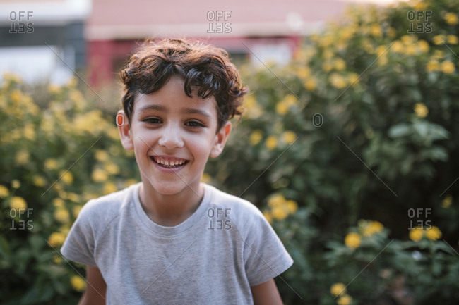 Little boy with happy curly hair in a park