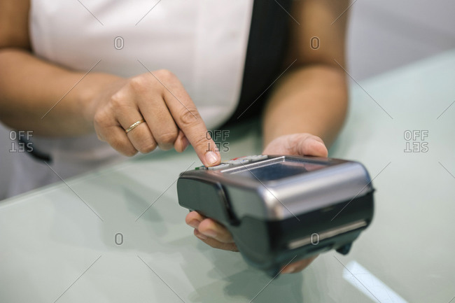 Woman hands charging with credit card at a counter