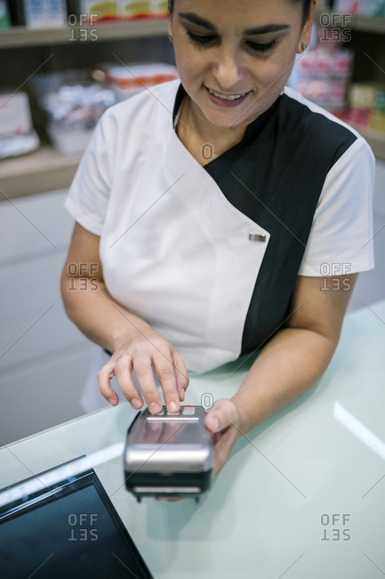 Pharmaceutical woman charging with credit card in a pharmacy