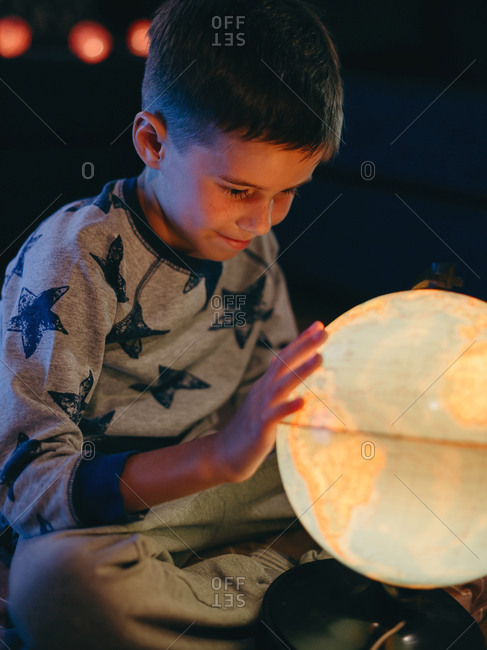 Portrait of little boy exploring a large globe in a dark room and dreaming about new travel.