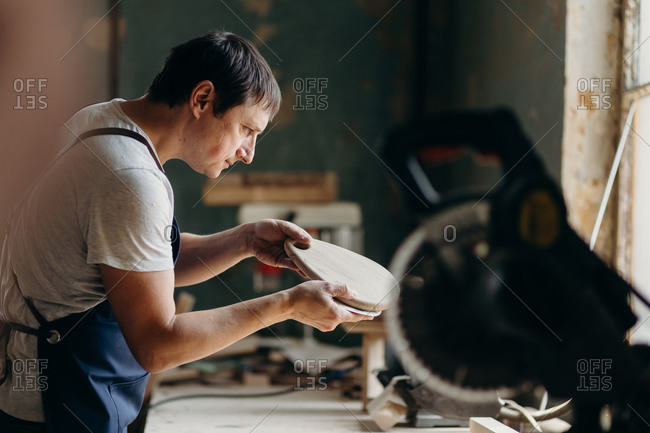A carpenter touching and inspecting wooden board in a workshop. Process of creating a wooden furniture.