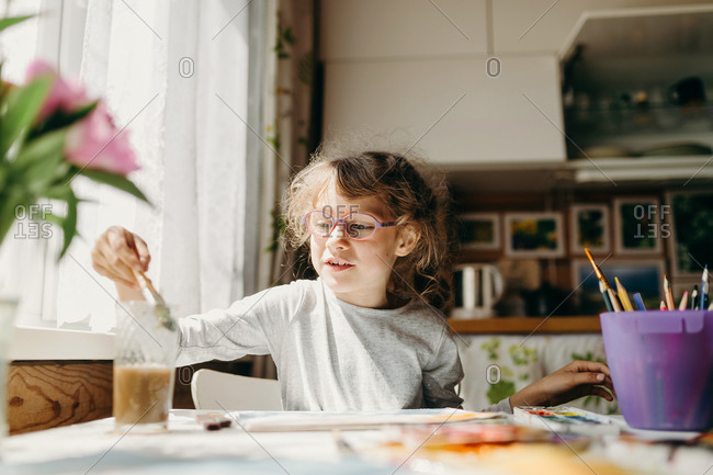 Cute little girl in glasses drawing a picture at home. Home education concept