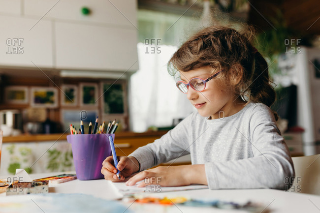 Focused preschool child enjoying creative art hobby at home. Kid doing homework in sunny room