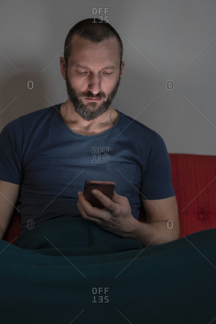 Hipster man using smartphone on sofa
