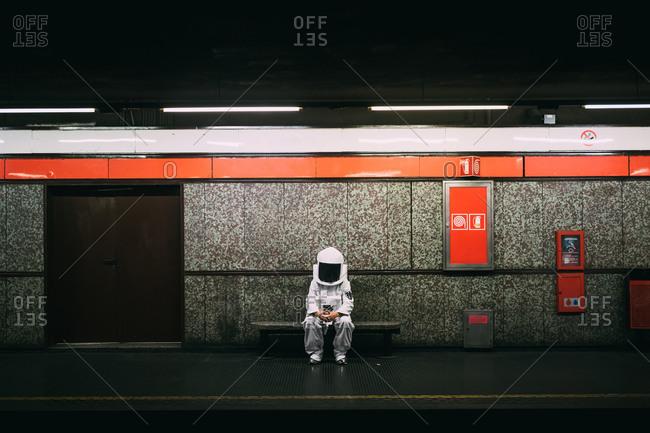 Astronaut waiting on train platform