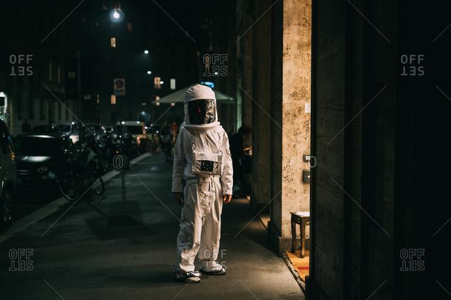 Astronaut walking on pavement at night