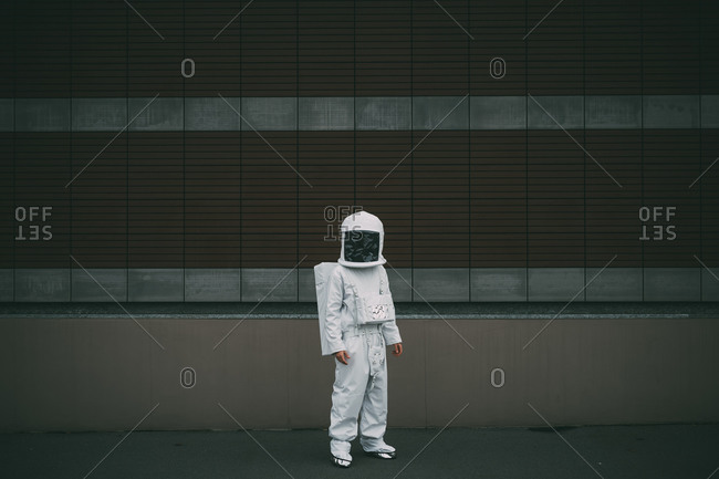 Astronaut standing against striped concrete wall
