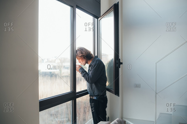 Businessman smoking out of window
