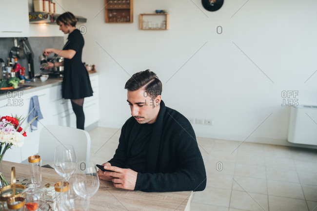 Businessman using smartphone, colleague making coffee in background