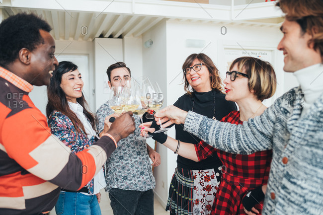 Friends toasting white wine in loft office