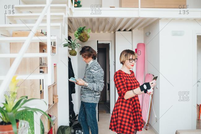Woman using smartphone, man reading book in loft office
