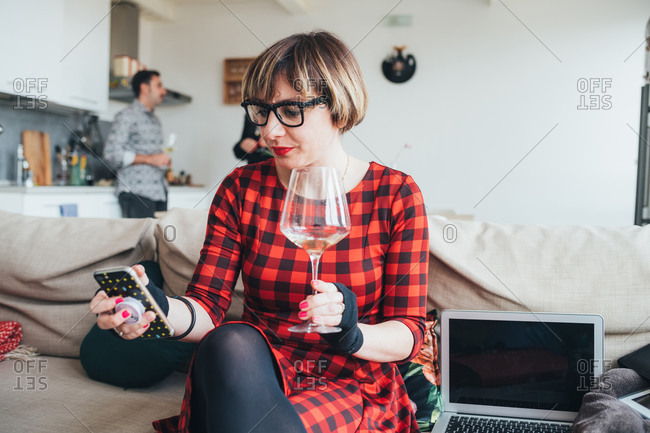 Woman using smartphone at party, friends talking in background