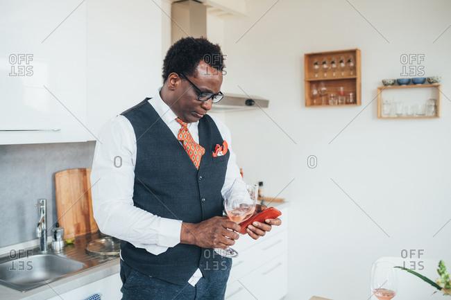 Businessman using smartphone in kitchen
