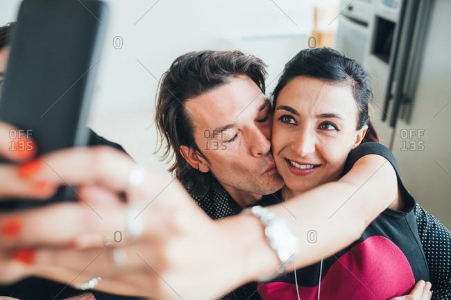 Couple taking selfie in loft office
