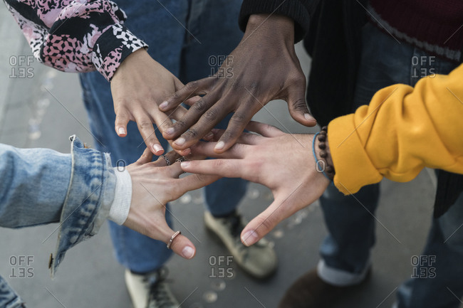 Four female and male young adult friends bringing hands together, close up of hands