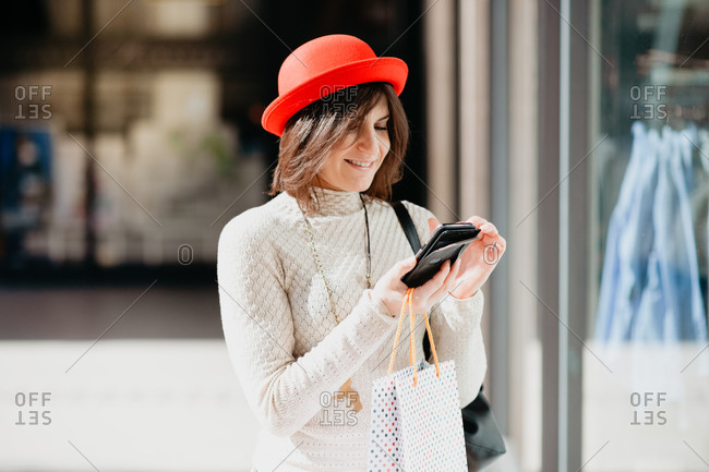 Female shopper using smartphone in front of shop
