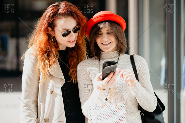 Female shoppers using smartphone in front of shop